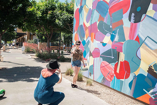 Friend taking photo in front of Zinburger Mural