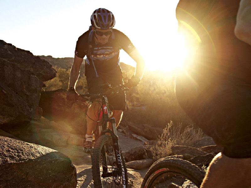 A cyclist rides a mountain bike between two large boulders as the sun sets behind him in San Tan Mountain Regional Park near Gilbert, Arizona.